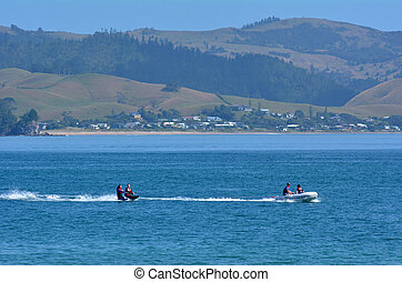 People water skiing over Mercury Bay New Zealand