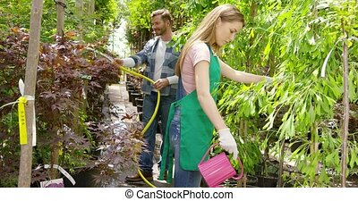 People watering flowers - Man and woman watering and taking...