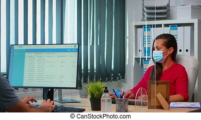 People wearing face masks back at work in office with new normal. Team working in workspace in personal corporate company typing on computer keyboard looking at desktop respecting social distancing.