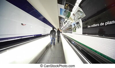 people will quickly go through corridor on horizontal escalator in Paris airport