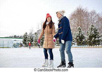 happy couple ice skating on rink outdoors - people, winter,...