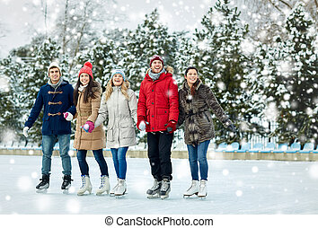 happy friends ice skating on rink outdoors
