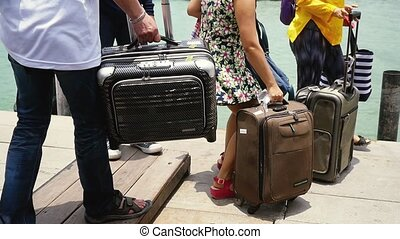 People with a backpack and carrying luggage arriving the...
