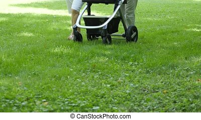 People with baby carriage walking in a green park. Panning shot