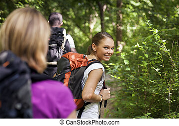 people with backpack doing trekking in wood - group of man...