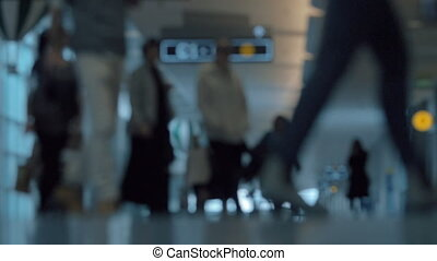 People with baggage in airport hall, defocus