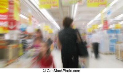 People with carts in a supermarket. Motion blur. Time lapse.