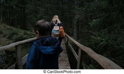 People with children slowly pass through the old wooden...