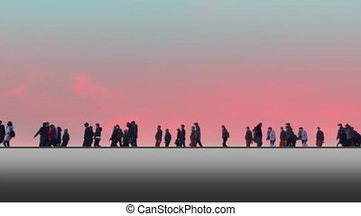 People with children walk and ride bikes against sunset sky