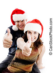 people with christmas hat showing thumbs up