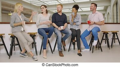 People with coffee listening to their colleague