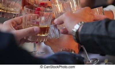 People with glasses of alcohol and glasses of whiskey celebrate at the table. Hands of people with glasses of whiskey close-up. Shallow depth of field