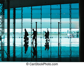 People with luggage walking at airport