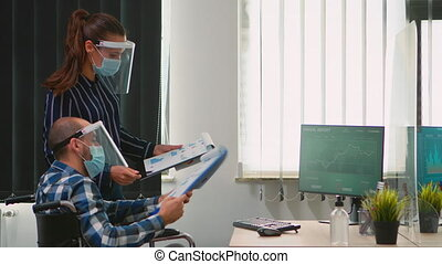 Business people wearing protective mask in new normal office making strategy, businessman sitting in wheelchair Team working in profesional workspace in corporate company during covid-19 pandemic.