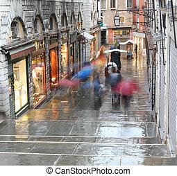 People with umbrellas in Rialto Bridge in Venice Italy while raining