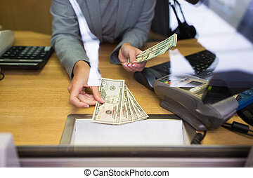 clerk giving cash money to customer at bank office - people,...