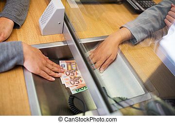 clerk giving cash money to customer at bank office