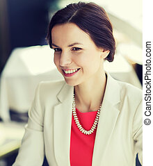 happy woman sitting at table in restaurant