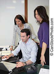 People working around a computer