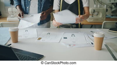People working in fashion designing studio holding sketches...