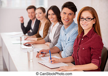 People working together. Group of young people sitting together at the table and smiling at camera
