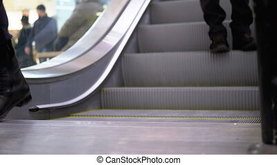 People's Feet go Down the Escalator Lift in the Mall. Shopper's Feet on Escalator in Shopping Center