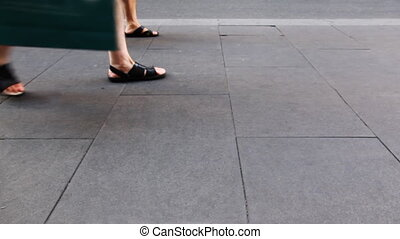 people's legs in summer shoes go pavement of stone slabs