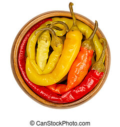 Peperoni pickles, pickled whole chili peppers in wooden bowl