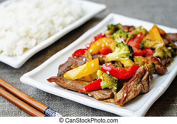 pepper broccoli beef stir fry on a grey background. the...