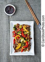 pepper broccoli beef stir fry on a dark background. the...
