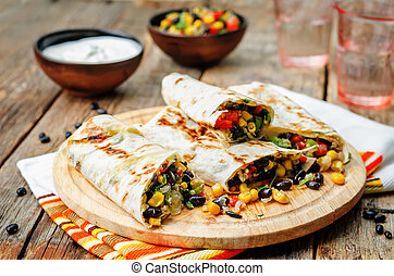 pepper corn black bean quinoa burritos on a dark wood...