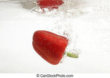 Pepper falling into water.