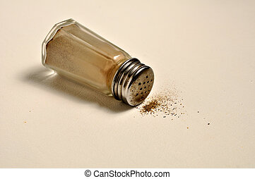 Pepper shaker - A glass pepper shaker is laying on its side.