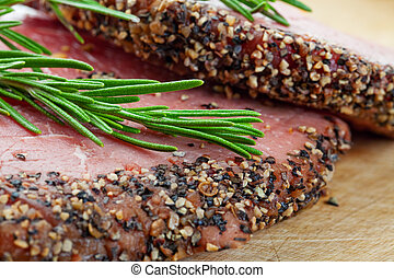 Two raw, eye of round, Alberta beef steaks, encrusted with pepper & spices and topped with fresh rosemary. BBQ ready! Shallow depth of field.