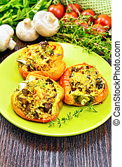 Pepper stuffed with mushrooms and couscous in plate on wood