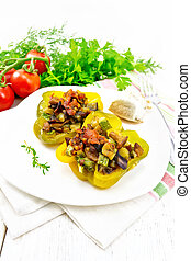 Pepper stuffed with vegetables in plate on light wooden board
