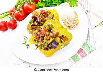Pepper stuffed with vegetables in plate on white wooden board