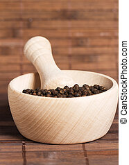 peppercorns in a wooden mortar on wooden background