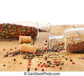 Peppercorns in glass bottles on wood table