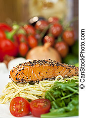 Peppered salmon fillet with spaghetti pasta tomatoes and green salad
