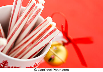 Peppermint stirrers in white cup with red snowflakes.