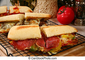Hot toasty submarine sandwiches with beef, salami, pepperoni sausge, melted cheese, and vegetables.