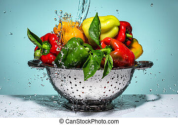 Peppers of different colors in a colander.