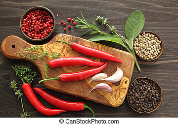 Peppers, spices and herbs on a wooden kitchen board.