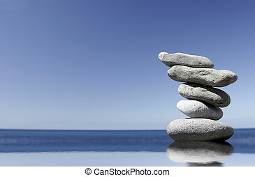 Pepple Stack in Water - Stack of volcanic pebbles in calm...