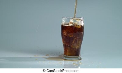 Pepsi is poured into a glass with ice. Blue background -...