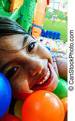 pequeno, bolas, coloridos, menina sorridente, tocando, mentindo