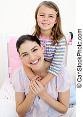 pequeno, dela, abraçando, mãe, menina sorridente