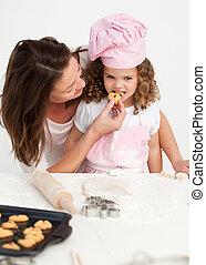 pequeno, dela, provando, biscoito, mãe, menina