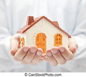 pequeno, laranja, casa brinquedo, em, mãos